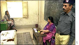 Officers man an empty polling station in central Karachi