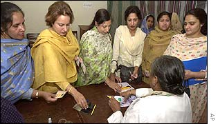 Women voters show identity cards to a polling officer to cast their vote inside a polling station in Lahore