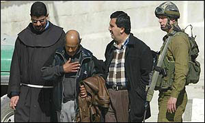 Palestinian officer (second left) is handed over to Israeli forces after leaving the church