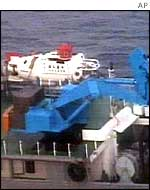 A submarine, white in the background, and a crane, blue in front, are prepared on a salvage ship before the start of the underwater survey