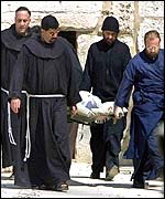 Priests taking out the body of a Palestinian killed on Thursday