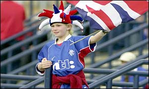 A young Rangers fan waves a Union flag as she enters Hampden Park