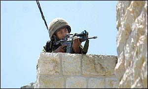 An Israeli sniper aims his gun towards the scene of an explosion at a house near Manger Square in Bethlehem