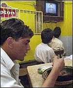 A man enjoys his dinner in a restaurant as President Musharraf addresses the nation on television