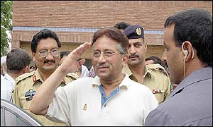 President General Pervez Musharraf (centre) salutes in response to voters slogans at a polling station