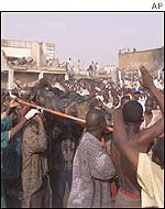 People carry the body of a deceased person to a makeshift ambulance in Kano