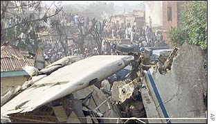 The wing of the crashed plane of the EAS airlines is poised on the roof of a house in Kano
