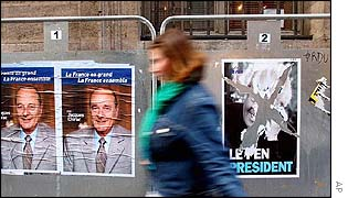 Woman passes campaign posters