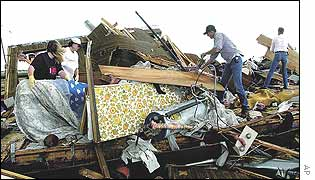 Residents and volunteers search through the debris of a home in Happy, Texas