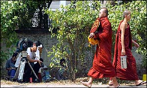 Buddhist monks walk past press photographer outside Aung San Suu Kyi's home