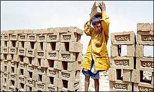 Child carrying bricks on construction site