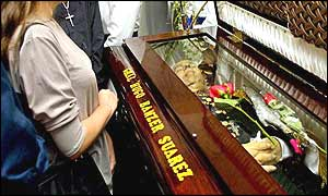 Mourners viewing coffin before lid is finally closed