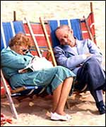 A couple sleeping on deckchairs
