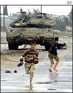 Palestinian children throw stones at an Israeli tank
