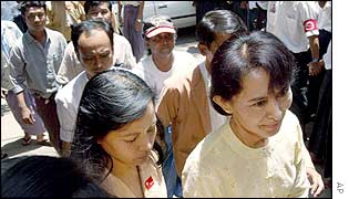 Aung San Suu Kyi (right) smiles as she arrives at her party headquarters, 7 May 2002