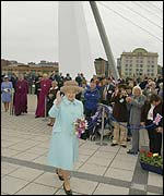 The Queen waves as she walks across the 'Winking Eye' bridge