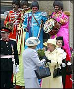Wellwishers in Beatles costumes greet the Queen