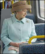 The Queen looks out of the window on a metro train