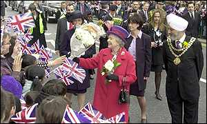 The Queen is given flowers by the London crowd