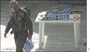 An Israeli soldier starts clearing food set out for those expected to leave the church after the talks stalled