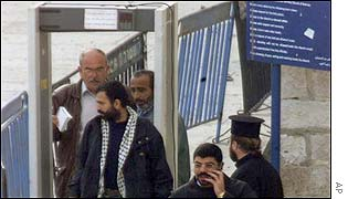 The first of the 13 Palestinians to be deported passes a metal detector as he leaves the Church of the Nativity in Bethlehem at daybreak on Friday