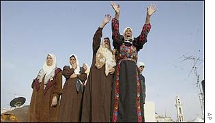 From a rooftop in Bethlehem relatives wave and cry out the names of Palestinian family members as they exit from the Church of the Nativity