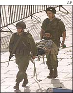 Israeli soldiers carry militant on a stretcher