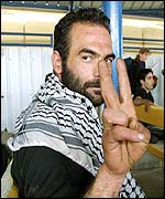 Militant at Gaza crossing point shows V-sign