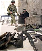Israeli soldiers inspect guns and ammunition found in the Church of Nativity