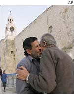 Two Palestinian men embrace after Israeli troops withdraw from Manger Square
