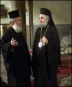 Greek Orthodox Patriarch Irineos I (R) talks with an unidentified priest as they inspect the damage