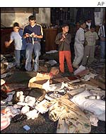 Palestinians inspect debris left behind by those besieged in the Church of the Nativity