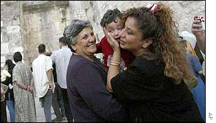 Mother kisses her child outside the Church of the Nativity