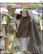 Kashmiri woman passes an Indian soldier