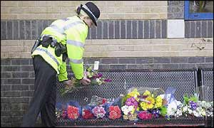 A police officer lays flowers at station