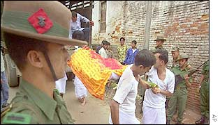 Nepalese soldiers look on as body of comrade killed in action is taken for cremation
