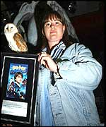 31-year-old, Toni Preece (right), from Eltham, south east London is presented with a plaque, certifying her purchase of the very first copy in Britain of the new Harry Potter DVD