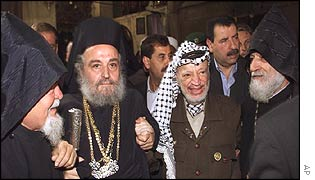 Yasser Arafat flanked by priests in Bethlehem's Church of the Nativity