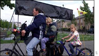 A family in Oegstgeest cycle pass an election poster covered in black
