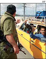 Israeli soldier checks the permit of a taxi driver