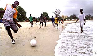 Youths playing soccer on a beach in the capital Freetown