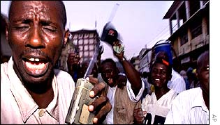 A supporter of President Kabbah reacting to  election news on the radio as he took an early lead