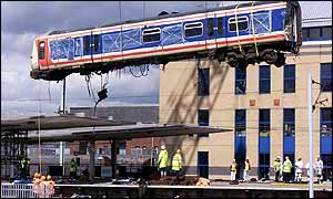 The carriage derailed in the Potters Bar crash is hoisted above the station by a crane
