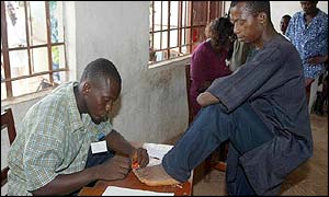 An election officer puts indelible ink on the toe of an amputee voter
