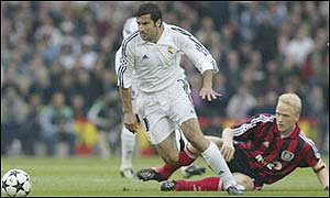 Real Madrid's Luis Figo slips past Carsten Ramelow of Bayer Leverkusen