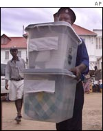 A police officer brings two ballot boxes to be handed over to the National Election Commission in Freetown