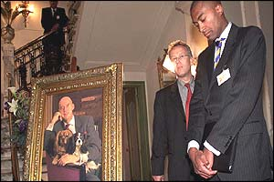 Joao Varela (right) number two on the Pim Fortuyn party list stands next to the dead politician's portrait