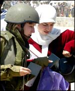 Israeli soldier checking Palestinians