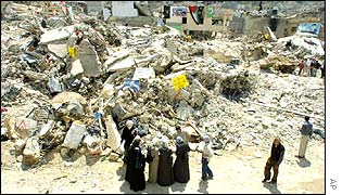 Residents of Jenin refugee camp walk past the rubble of flattened houses