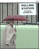 Woman with umbrella passes polling station